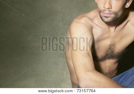 Bare-chested Hispanic man sitting on floor
