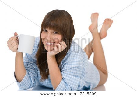 Female Teenager In Pajamas With Cup Of Tea