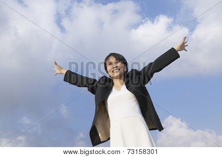 Asian businesswoman with arms outstretched