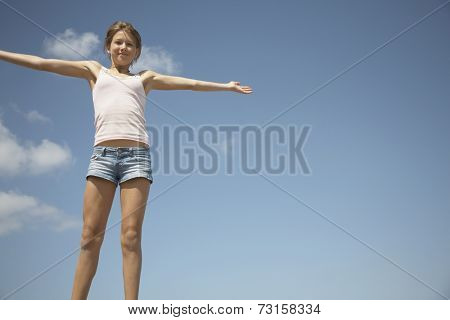 Teenage girl with arms outstretched under blue sky