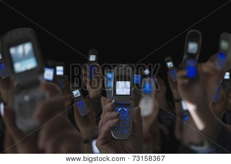 People holding open cell phones up in air