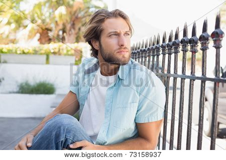 Casual man sitting and thinking on a sunny day in the city