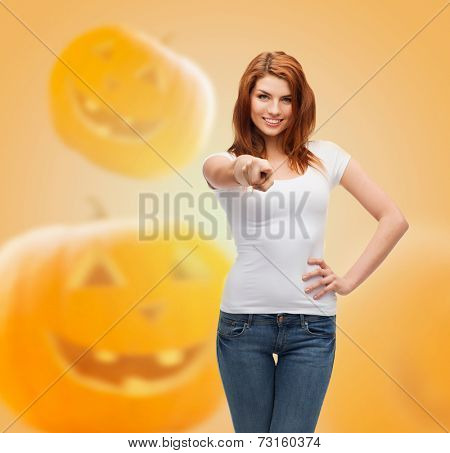 holidays, advertisement, gesture and people concept - smiling young woman in blank white t-shirt pointing finger at you over halloween pumpkins background