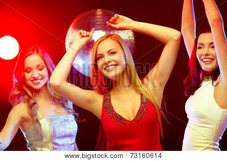 party, new year, celebration, friends, bachelorette party, birthday concept - three beautiful women in evening dresses dancing in the club