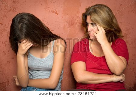 Teenager problems - Sad crying teenage girl and her worried mother