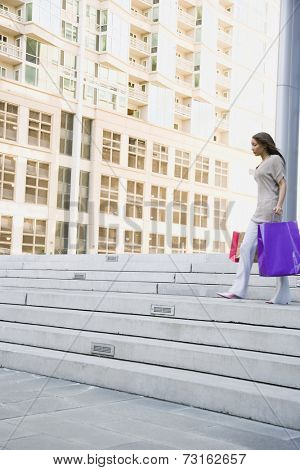 African woman carrying shopping bags down steps