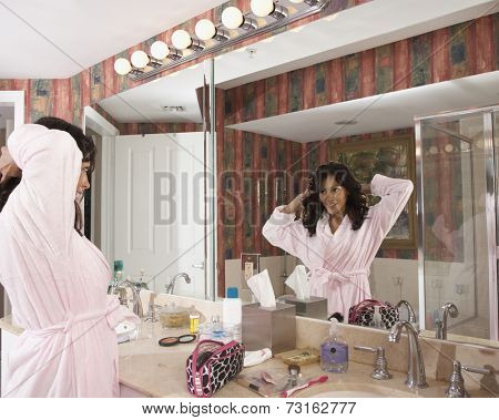 Hispanic woman looking in bathroom mirror