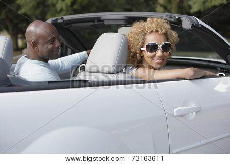 African couple driving convertible car