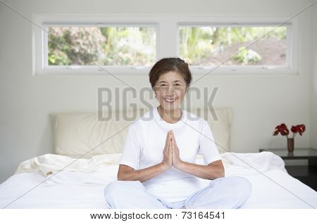 Senior Asian woman meditating on bed