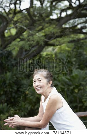 Senior Asian woman leaning on balcony railing