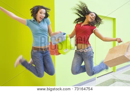 Multi-ethnic teenage girls jumping with shopping bags