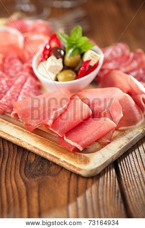 meat antipasti Platter of Cured Meat,   jamon, olives, sausage, salami  on old wooden board