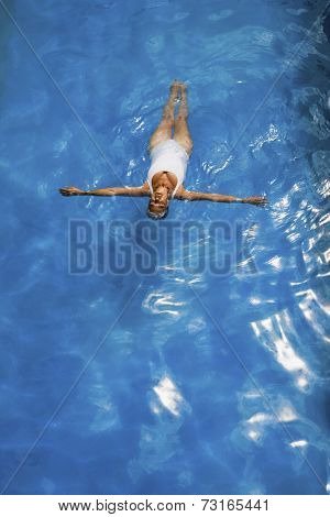 Senior woman floating in swimming pool