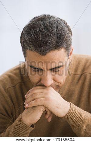 Hispanic man leaning head on hands