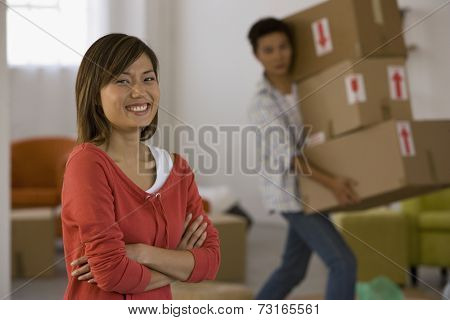 Asian woman laughing while husband carries boxes