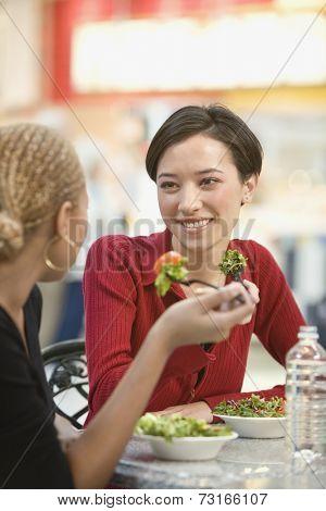 Mixed Race women eating salad