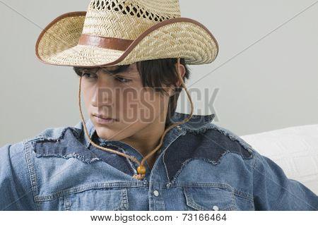 Young Hispanic man wearing cowboy hat