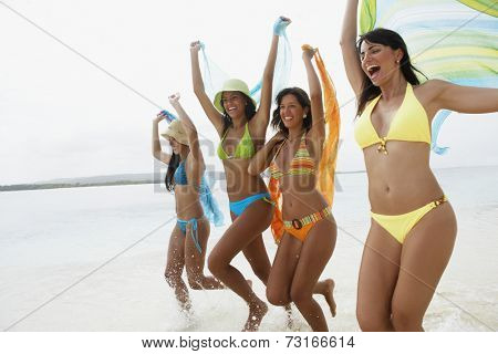 South American women jumping on beach