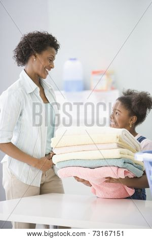 African American mother and daughter doing laundry