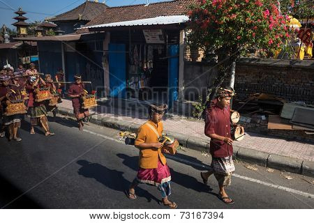 SEPTEMBER 18, 2014 - BALI, INDONESIA: A troupe of Balinese musicians leads a parade through the village heading to a temple for ceremonial prayers. Hinduism is the religion of the Balinese people.