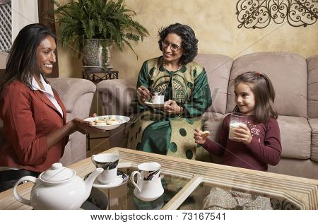 Multi-generational Indian female family members having snack