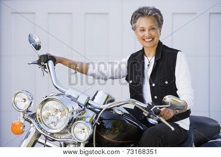 Senior African American woman sitting on motorcycle