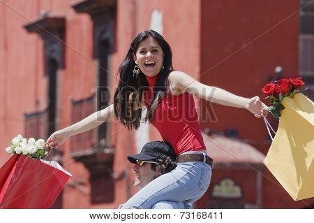 Hispanic woman riding on boyfriend's shoulders