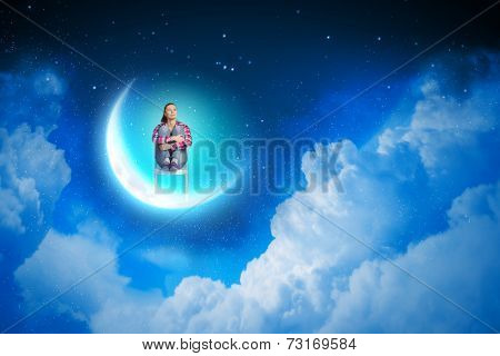 Young pretty girl sitting on moon in sky