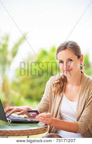Portrait of a pretty young woman working on her computer on a terrace of her house - paying online with her credit card