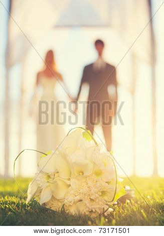 Close up of Wedding Bouquet. Focus on Flowers. Bride and Groom in Background.