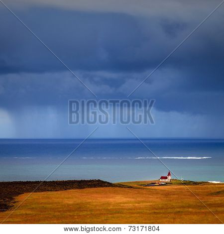 Icelandic church on the coast with rain in the background