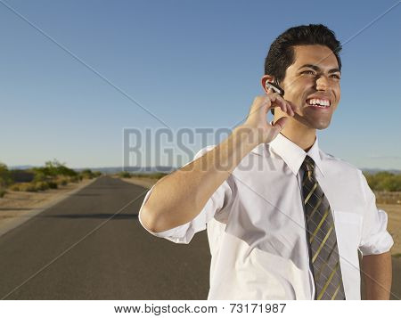 Hispanic businessman using hands-free device
