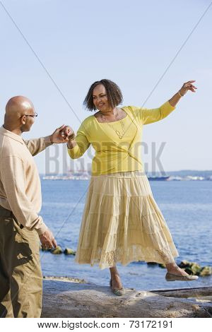 African American woman holding husband's hand for balance