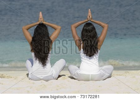 Hispanic women practicing yoga at beach