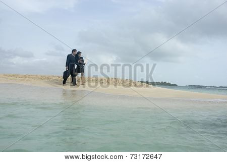 Hispanic businesspeople walking on beach