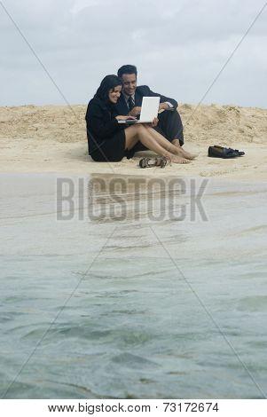 Hispanic businesspeople working at beach