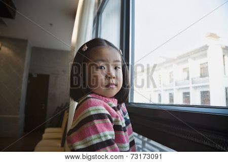 Asian girl next to window