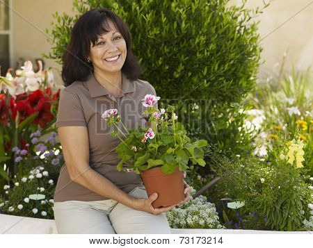 Hispanic woman holding potted plant