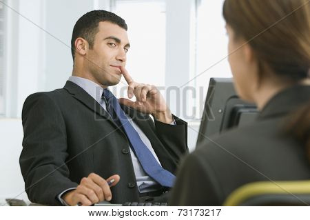 Hispanic businessman looking at coworker