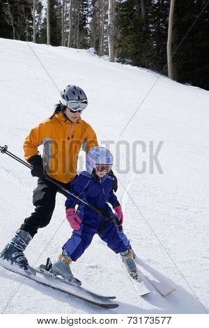 Asian mother and daughter skiing