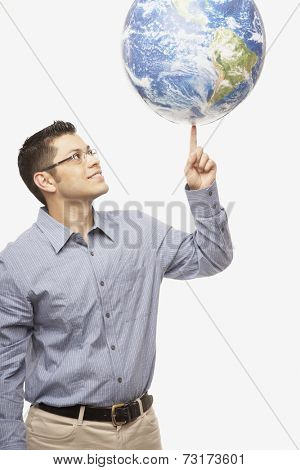 Hispanic man balancing globe on fingertip