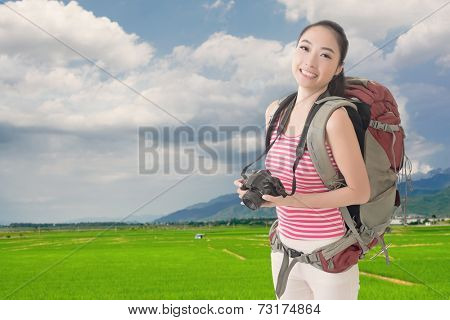 Happy smiling Asian young female backpacker with camera standing in front of farm in Hualien, Taiwan, Asia.