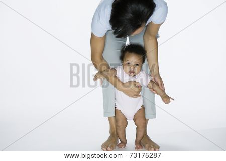 African American mother helping baby stand