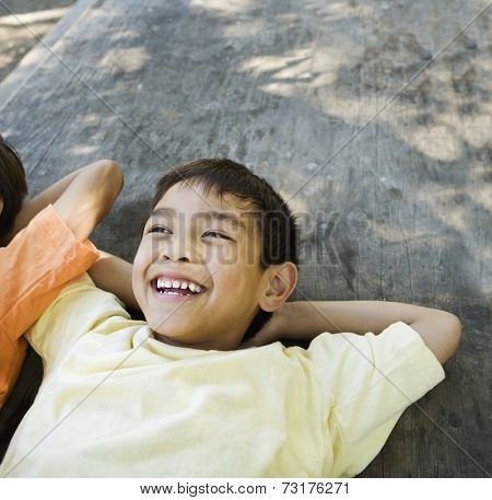 Asian boy laying with arms behind head
