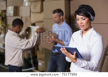 Pretty warehouse manager using tablet during busy period in a large warehouse
