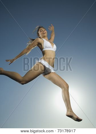 Asian woman in bathing suit jumping