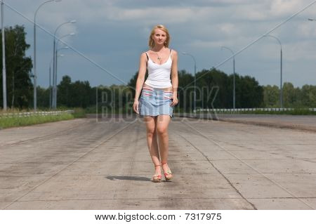 Young Woman Goes On A Highway.