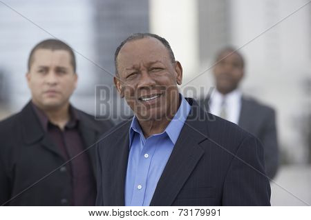 Senior African businessman with coworkers in background