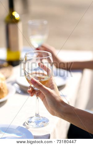 Friends enjoying drink at outdoor restaurant. Hand with glass, close-up