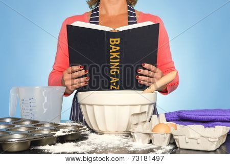 A woman standing at a kitchen worktop reading a BAKING A-Z book